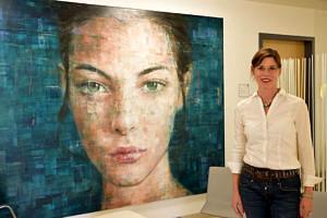 Beschäftigte in weißer Bluse steht vor einem riesen-großen Gemälde, auf dem das Gesicht einer Frau zu sehen ist.