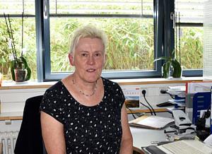 Eine ältere Dame mit kurzen weißen Haaren sitzt an ihrem Schreibtisch und blickt in die Kamera.