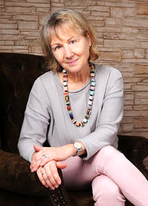 Portraitaufnahme von einer Frau: Sie sitzt auf einem braunen Sessel vor einer Backsteinwand und trägt eine Halskette aus großen bunten Perlen.