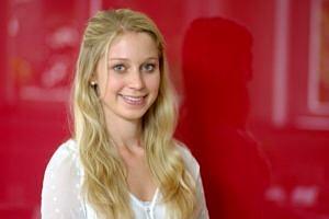 Eine Frau mit langen blonden Haaren vor einem roten Hintergrund