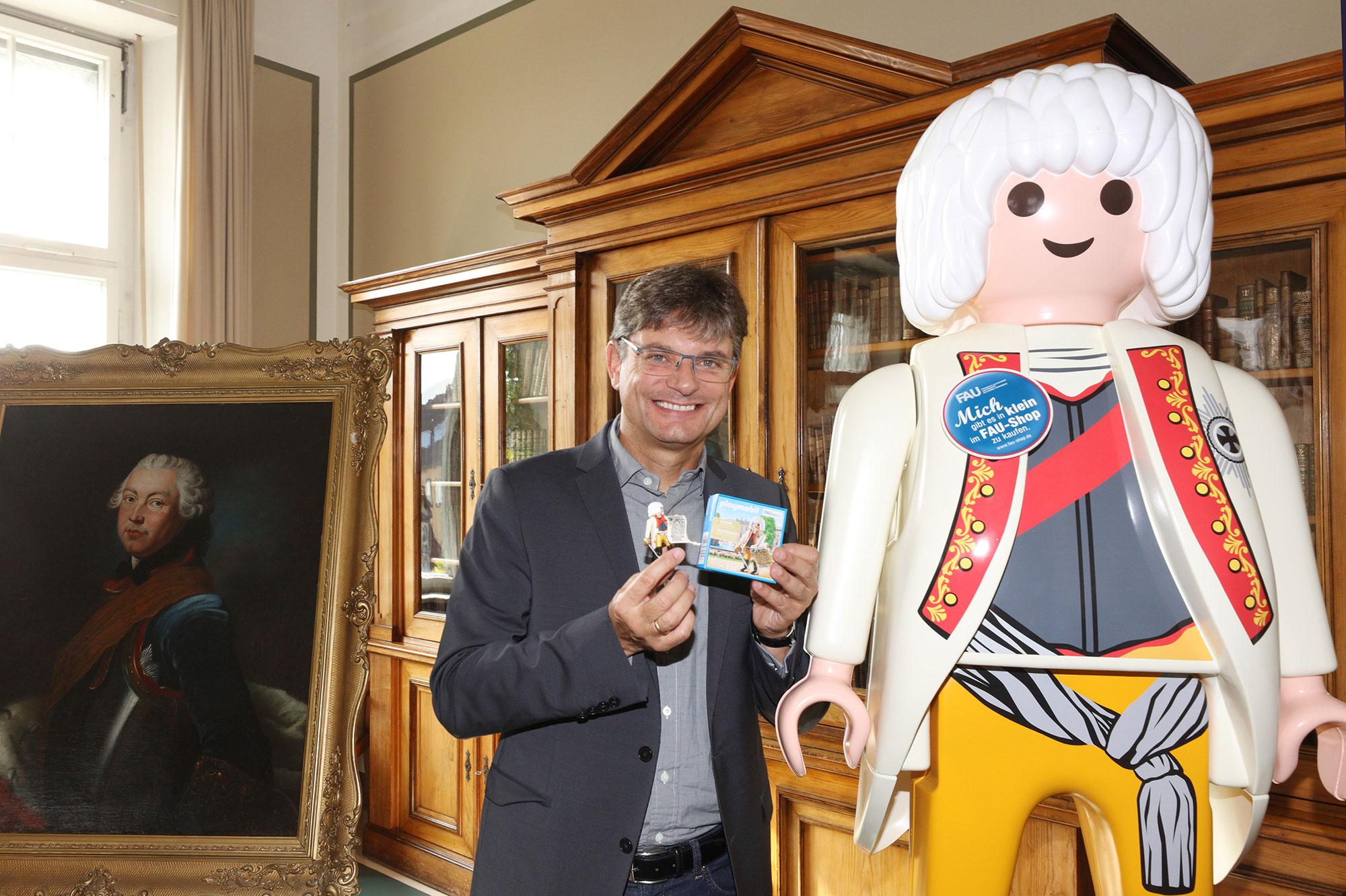 FAU President Prof. Dr. Joachim Hornegger presents the special edition PLAYMOBIL figure.