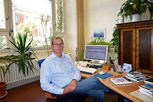 Ein Mann sitzt an seinem Schreibtisch und blickt in die Kamera: ein alter antiker brauner Schrank sowie verschiedene Pflanzen schmücken sein Büro.