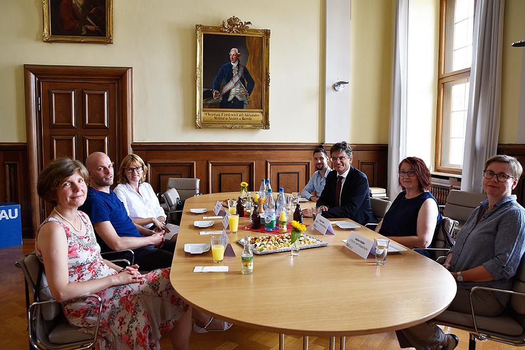 Insgesamt sitzen sieben Männer und Frauen um einen ovalen Tisch, der mit Getränken und Häppchen gedeckt ist, und blicken Richtung Kamera. An der Wand ist ein Gemälde in einem goldenen Rahmen zu sehen.