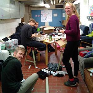 Vier Studierende befinden sich in einer Art Keller und packen dort Geschenke ein und blicken in die Kamera.