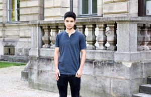 Ein Student mit dunklen Haaren steht vor einem steinernen Gebäude und blickt in die Kamera.