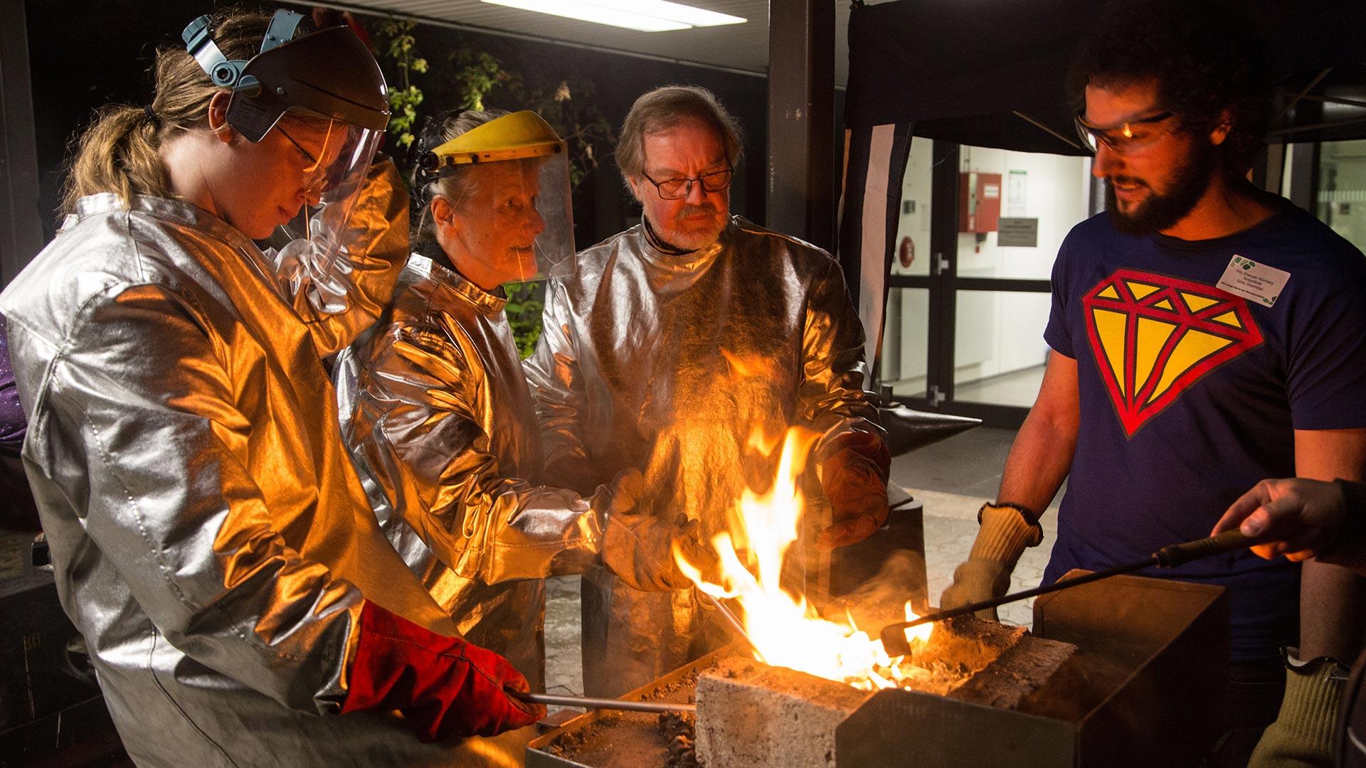 Vier Menschen stehen in Schutzanzügen an einem Feuer.