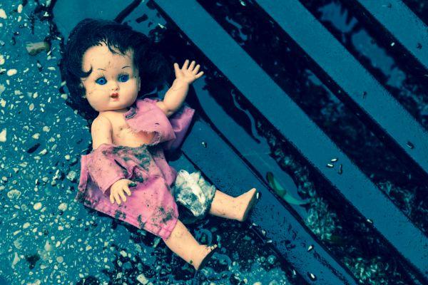 Puppe mit kaputter Kleidung liegt auf der Straße