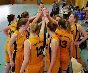Eine Basketballdamenmannschaft in orangefarbenen Trikots schlägt vor Spielbeginn ein.