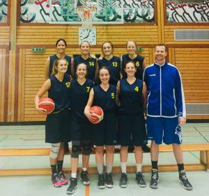 Acht Frauen in schwarzen Trikots und ein Mann in blauem Trikot portraitieren in einer Basketballhalle für das Foto und blicken in die Kamera.