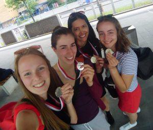 Vier Frauen machen ein Selfie und halten dabei solz ihre Goldmedaillen in den Händen.