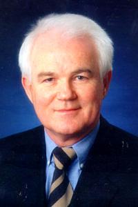 Portraitbild eines älteren Mannes mit weißem Haar im Anzug vor einem blauen Hintergrund