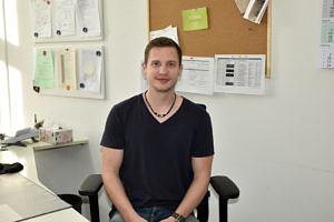 Ein jüngerer Mann sitzt im schwarzen Shirt auf einem Schreibtischstuhl und blickt in die Kamera.