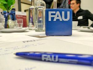 Tisch mit FAU-Würfel und FAU-Kuli