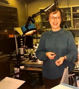 Eine junge Frau in einem Labor, die in die Kamera blickt.