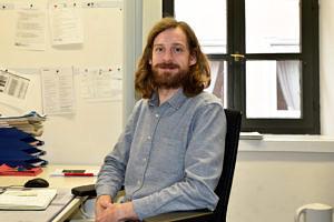 Ein junger Mann mit mittellangen Haaren und Vollbart sitzt an seinem Schreibtisch und blickt in die Kamera.
