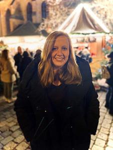 Eine Frau mit langen blonden Haaren steht in schwarzem Mantel auf einem Weihnachtsmarkt und lächelt in die Kamera.