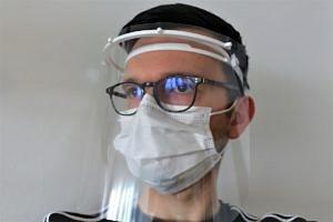 Mann mit Mundschutz und mehreren Visieren