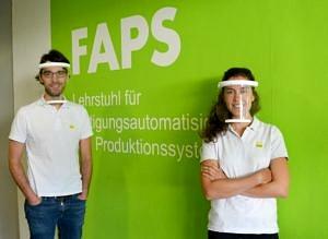 Eine Mitarbeiterin und ein Mitarbeiter des FAPS tragen Schutzvisiere.