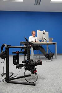 Im Vordergrund ein Stativ mit einer Kamera; im Hintergrund: ein Mann der am Arbeitsplatz sitzt. Der Hintergrund ist blau.