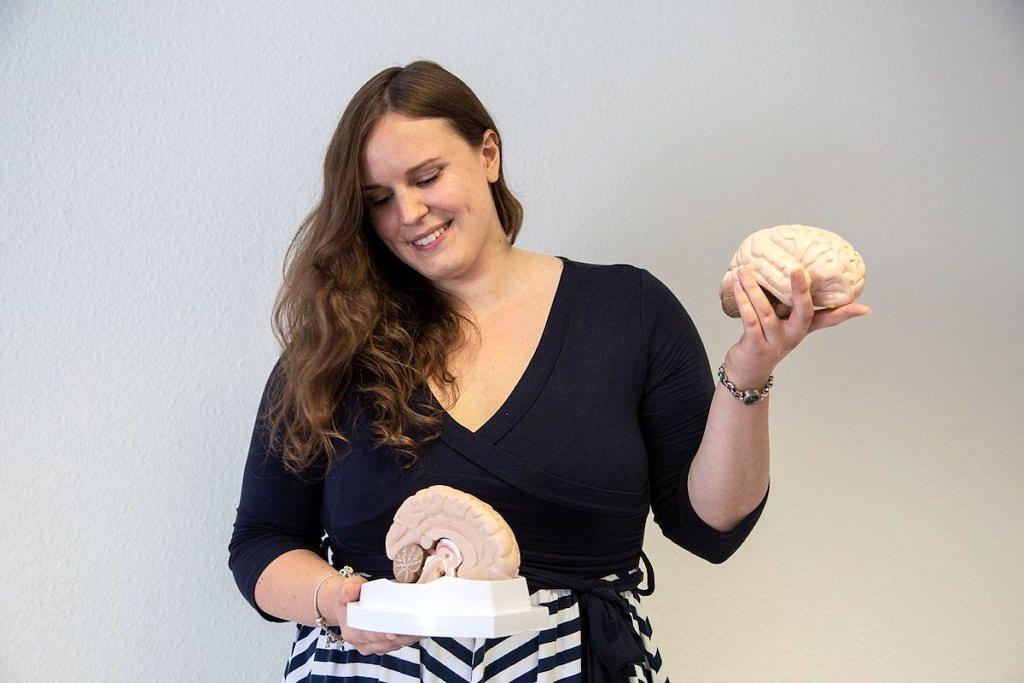 Prof. Dr. Louisa Kulke hält zwei Modelle des menschlichen Gehirns in der Hand