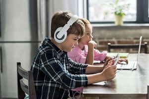 Zwei Kinder sitzen am Esstisch an Laptop und Tablet.