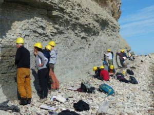 Studierende mit Helmen an Felswand