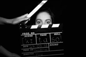 Eine Frau steht hinter einer Regieklappe.