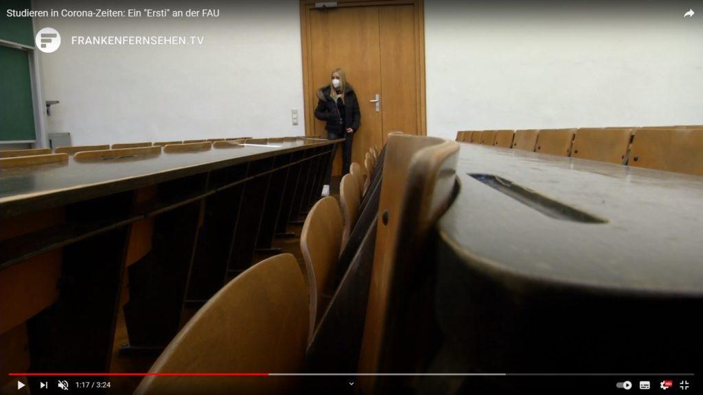 Leere Stuhlreihen, ganz hinten steht eine Studentin