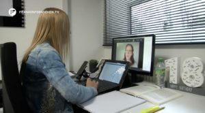 Studentin sieht eine Zoom-Vorlesung zuhause vor dem Laptop.