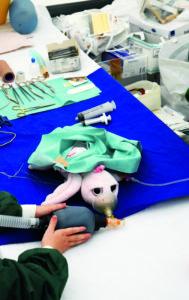 Eine Puppe auf einem Operationstisch.