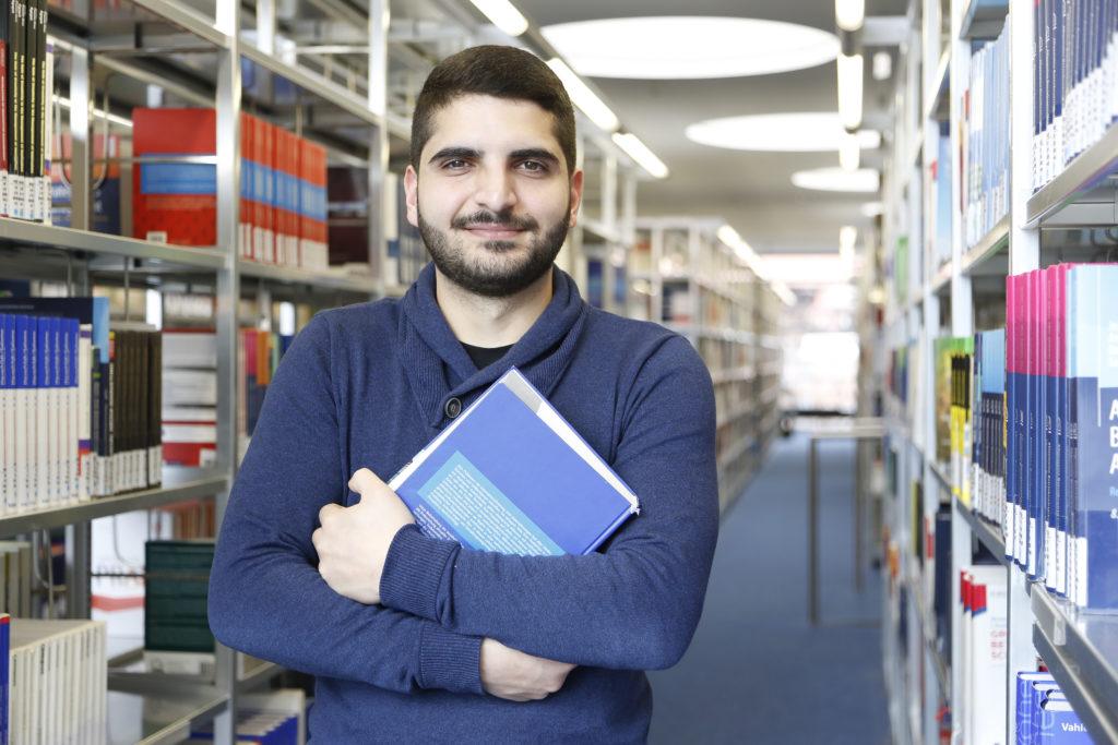 EIn Mann steht in einer Bibliothek.