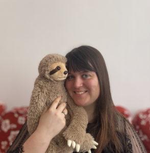 Portrait von Theresa mit einem Faultierkuscheltier