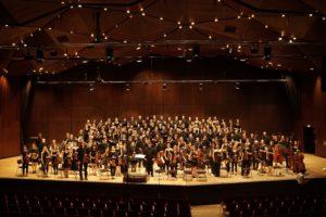Ein Orchester steht auf einer Bühne.