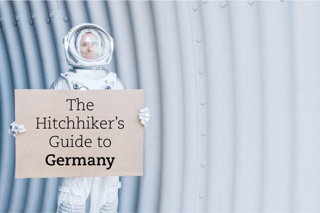 """Astronaut mit Schild in den Händen, auf dem """"The Hitchhiker's Guide to Germany"""" steht"""