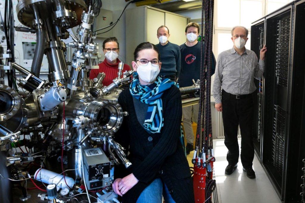 Portrait der fünf Arbeitsgruppenmitglieder in einem Labor mit großen Maschienen.