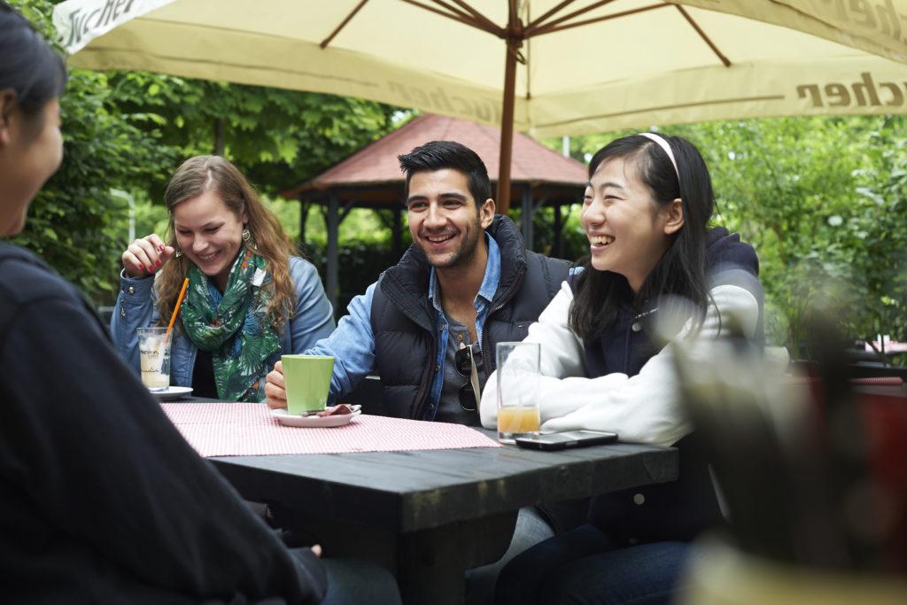 Studenten am Tisch in der Mensa.