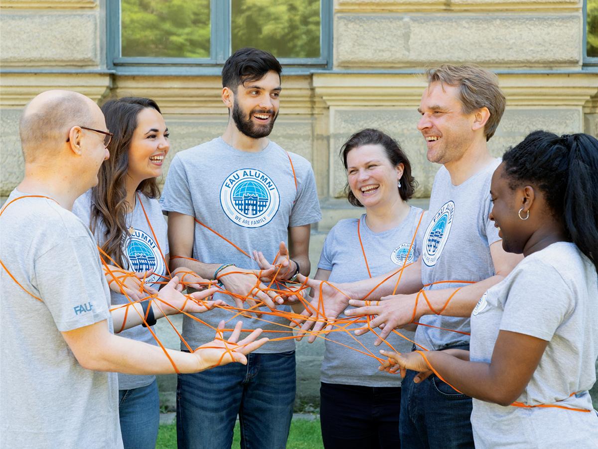 Eine Gruppe von Menschen, die durch ein orangenes Netz miteinander verbunden sind
