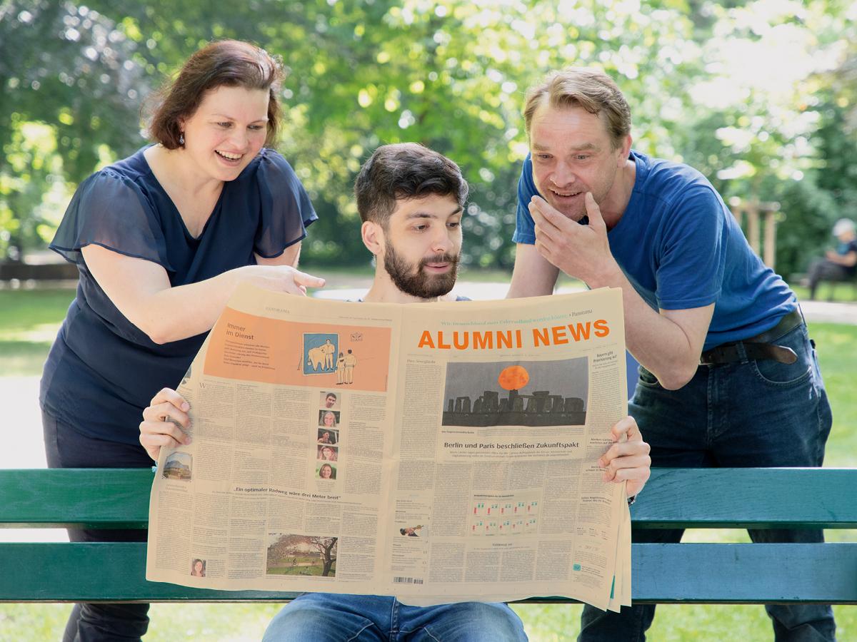 Drei Personen schauen erstaunt in eine Zeitung
