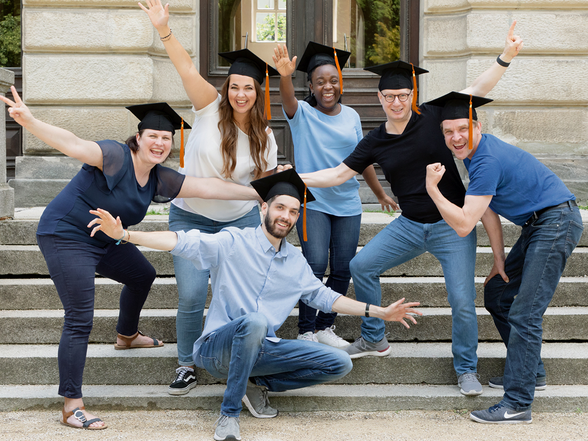 A group of happy people wearing graduation caps