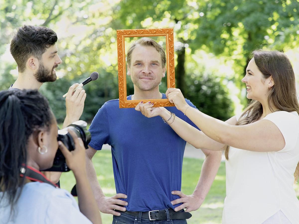 Mann in einem blauen T-Shirt schaut durch einen Bilderrahmen