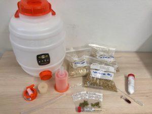Plastikbottich und verschiedene Tütchen mit Hopfen und anderen Zutaten fürs Bierbrauen