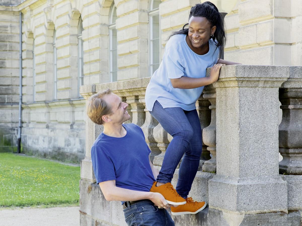 Ein Mann hilft einer Frau mit einer Räuberleiter auf eine Mauer