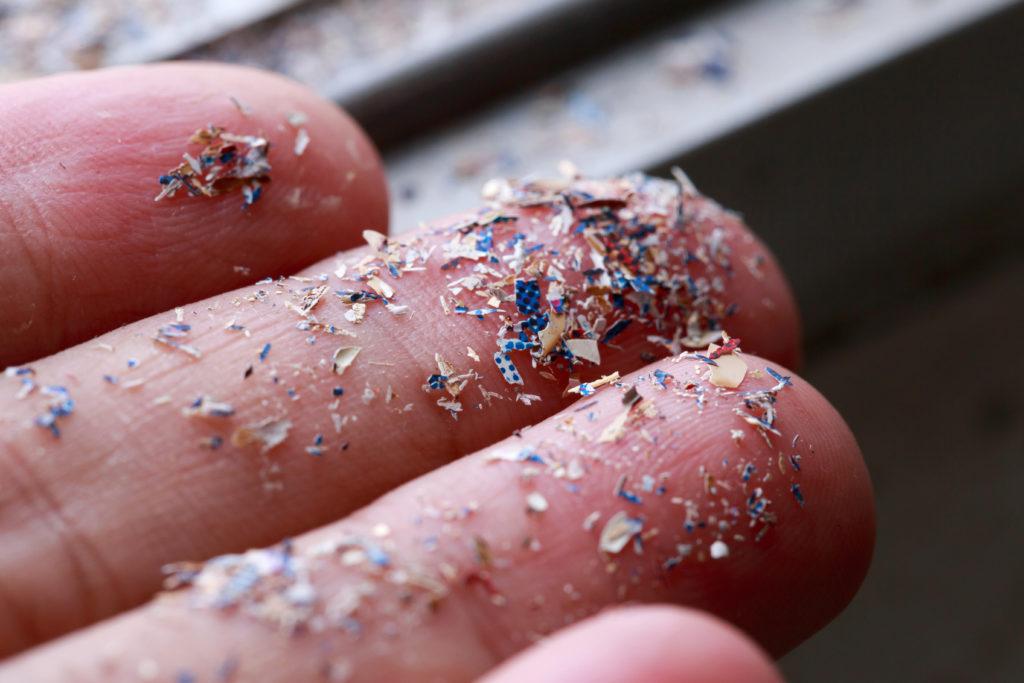 Hand hällt Plastikpartikel.