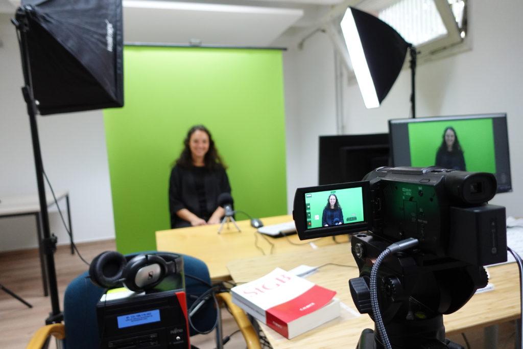 Frau sitzt vor einem Kamera in einem Greenroom.