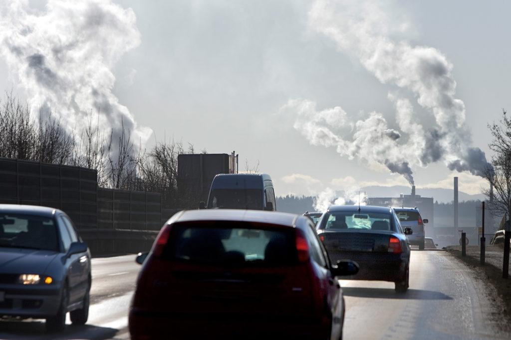Verkehr auf Straße, im Hintergrund Fabriken und Kraftwerke